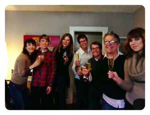 Uptown Studios Team Standing Holding Drinks Celebrating Thanksgiving In A Living Room