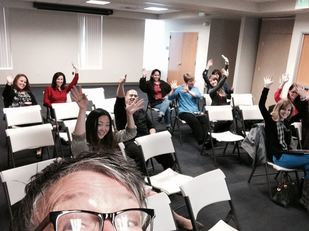 Tina Taking A Selfie Picture With Students Raising Their Hands In The Background Inside A Classroom Discussing Instagram For Businesses