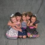 an image of 2 boys and 3 girls siblings kneeling on the ground and hugging each other