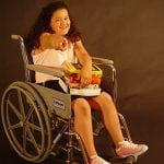 photo of a girl in a wheelchair pointing