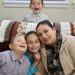 photo of a family on a couch with a child smiling in back