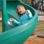 photo of a child on a slide in the playground