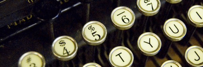 a close up image of an old timey typewriter with round worn out looking keys