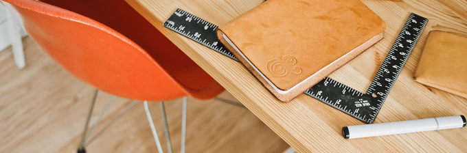 a top down image of a desktop with a leather bound notebook next to a square ruler and a pen