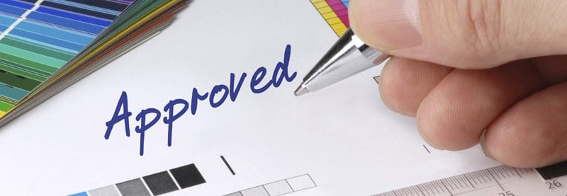 "a close up image of a hand holding a pen writing the word ""Approved"""