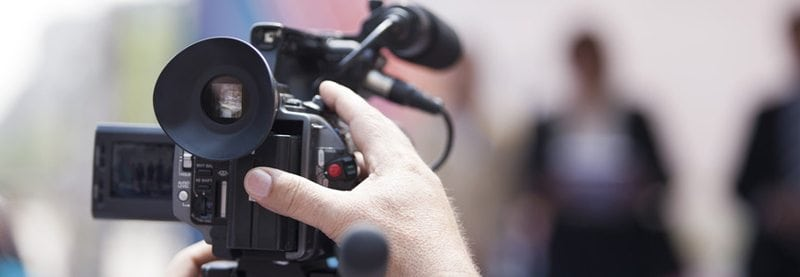 an image of a persons hand holding a video camera and hitting the record button with blurry people in the background