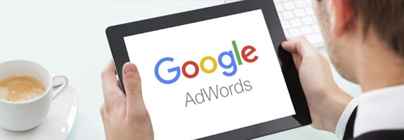 an over the shoulder shot of a man holding a tablet with the Google AdWords logo on it
