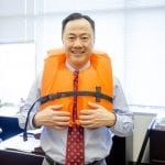 an image of a business man standing in his office and wearing an orange life jacket