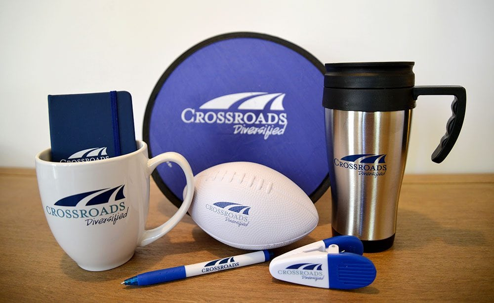 Crossroads Diversified swag, including a mug, foam football, magnet clip, pen, coffee thermos, and notebook