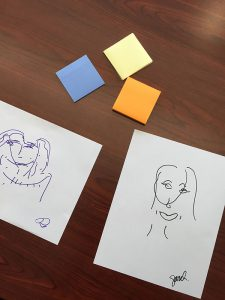 an image of some post-its on the page and two contour line sketches of human faces