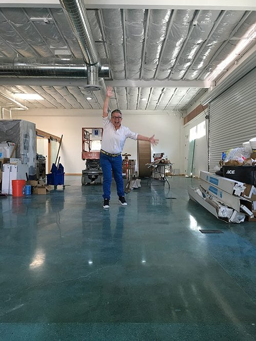 an image of Tina Reynolds jumping up and down on the brand new floors of our new warehouse office