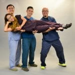 A fun photo of four SNAHC staff members in their work scrubs. Three men are holding up on woman who is laying horizontally across the three men's arms. All are smiling
