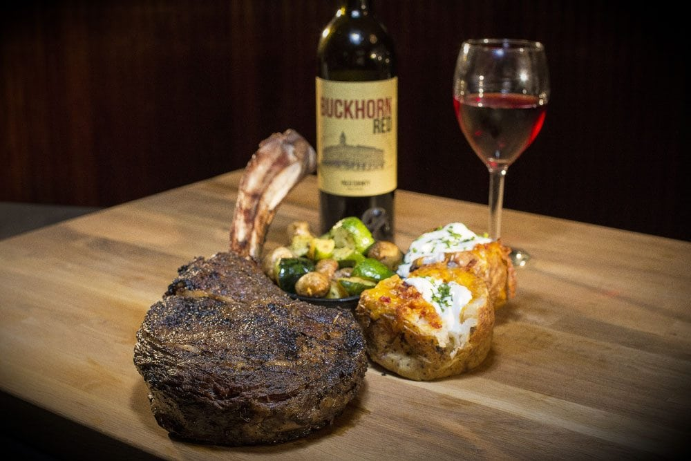 a nicely lit image of a large piece of steak, a baked potato, and some Buckhorn Steakhouse wine in the background, all on top of a large wooden cutting board