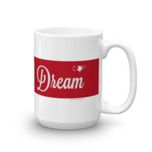 white coffee mug with red stripe and the word dream