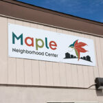 Sign Of Maple Neighborhood Center With Maple Leaf On Side Of La Familia Building