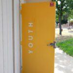 Yellow School Door With Youth Written On Door That Is Open