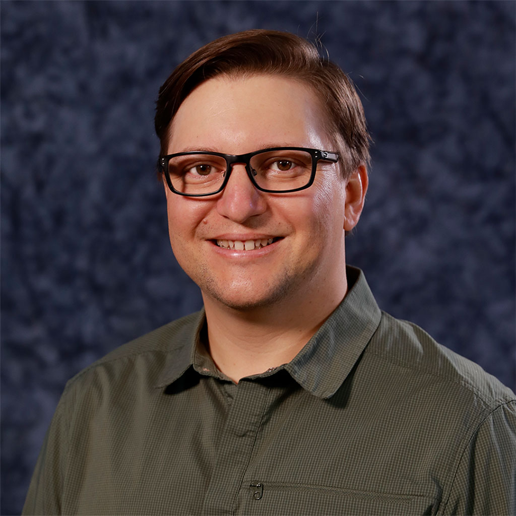 Brennan Grout Headshot Wearing Glasses Smiling With Green Collard Shirt And Dark Blue Background