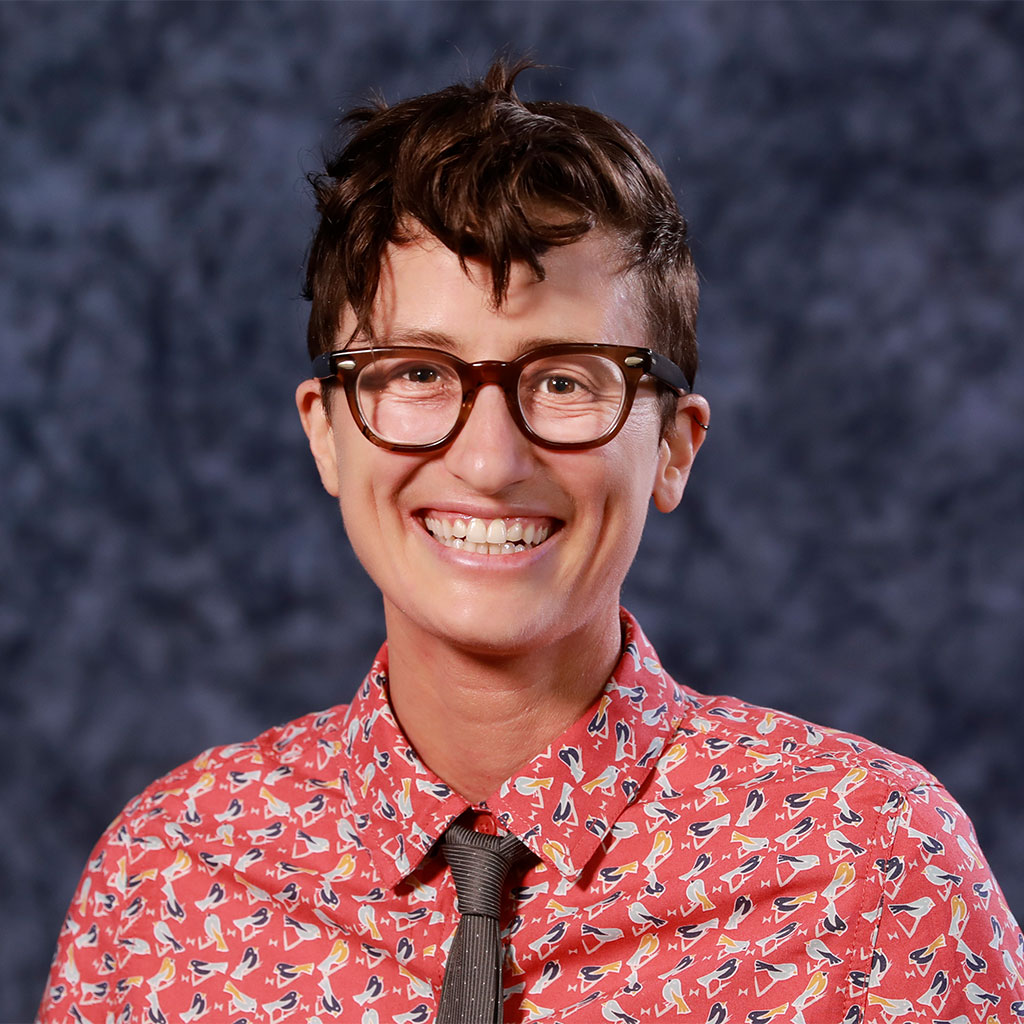 Jill Bruschera Headshot Smiling Wearing Red Collard Shirt And Tie With Blue Background